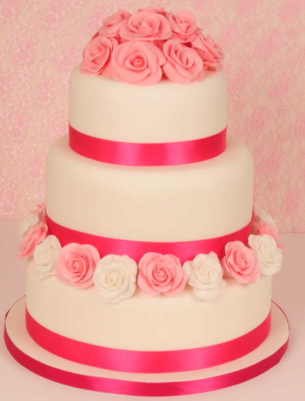 pink roses on white wedding cake with ribbons