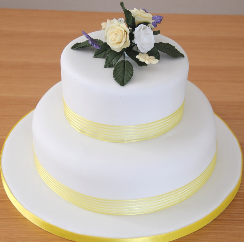 white and yellow 2 tier wedding cake with flowers